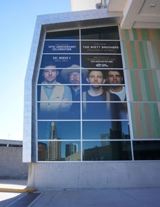 The windows above the Long Center entry courtyard are covered by our perforated vinyl window adhesive announcing the Grammy-nominated band The Avett Brothers upcoming concert on March 3.