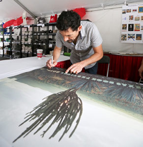 Artist Joel Salcido signs a festival poster featuring a beautiful print of his photograph. We're proud to work with Texas Book Festival, which gives a platform to talented, local authors and artists like Salcido.